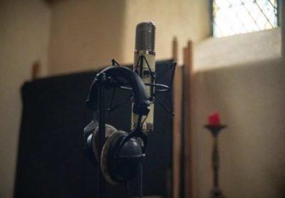 Casque pour écouter de la musique posé un micro, éclairés par le soleil à travers un vitrail